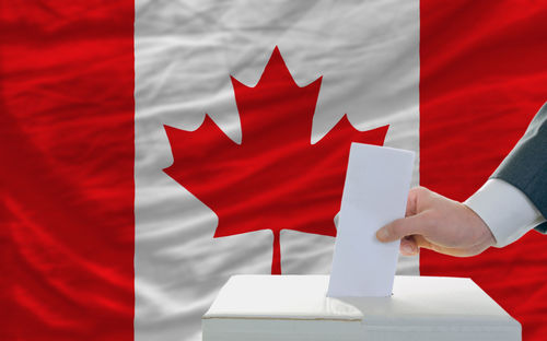 man-putting-ballot-in-a-box-during-elections-in-canada.jpg
