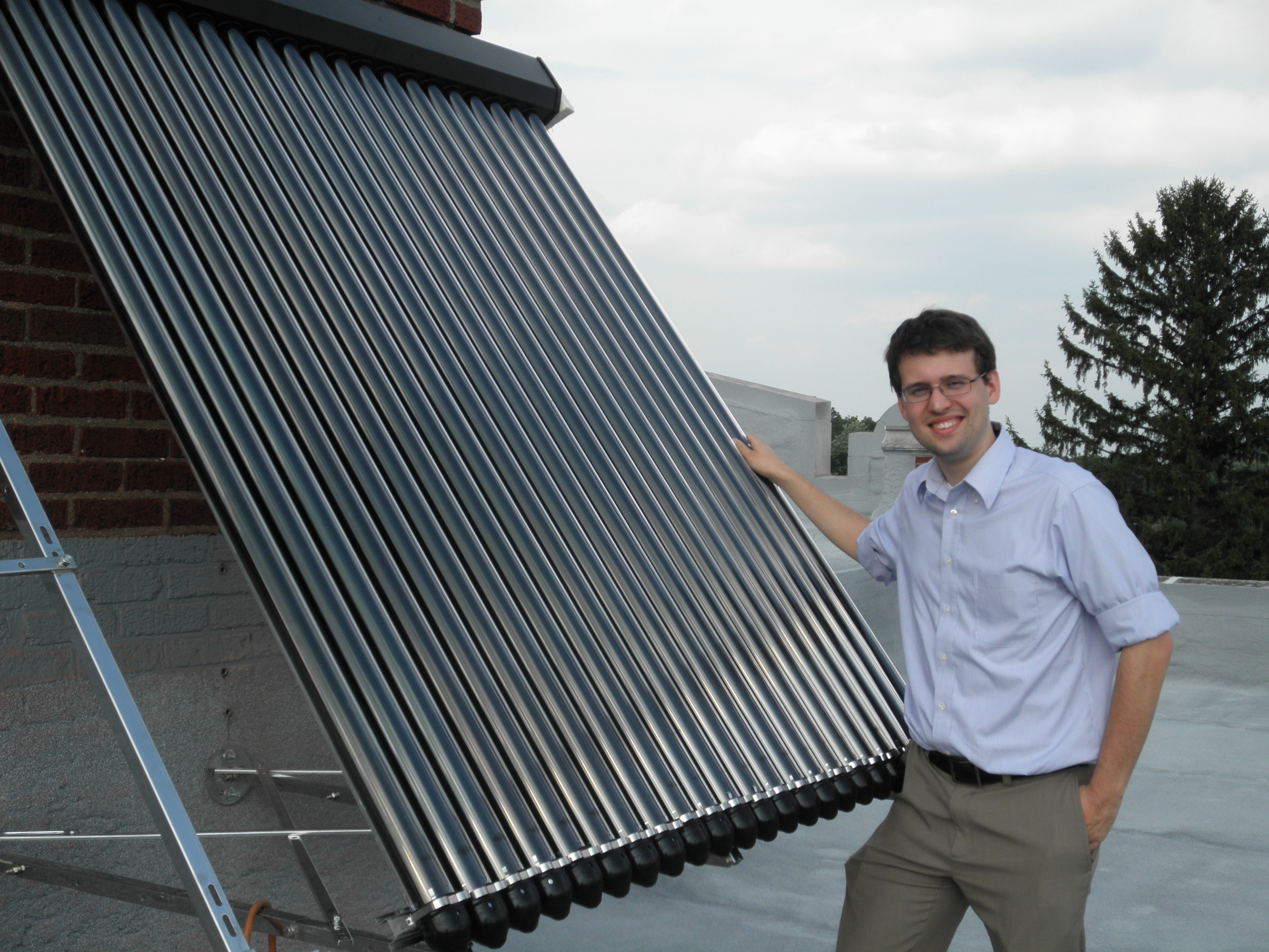 Brian Abels of Energy Optimizers USA standing next to a company installation of evacuated tubes in Ohio