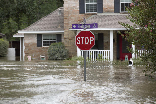 A stop sign stands above a flooded suburban street. In the background, a two-story home is flooded up to its front door and a water line on the side of the building reaches the first-story windows.