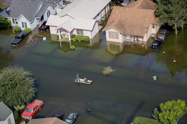 In an aerial image, two men drive a boat down a flooded residential street.