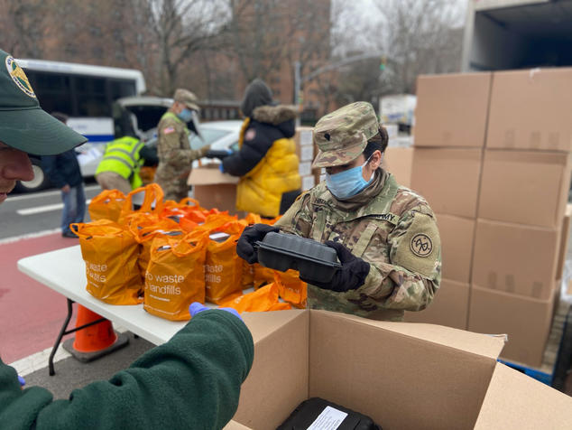 A woman wearing Army fatigues, gloves, and a mask stands at an outdoor table packing pre-made meals into reusable bags.