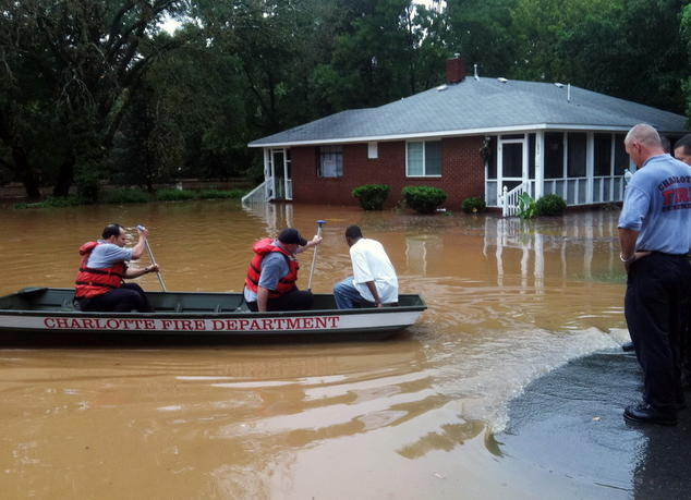 Firefighters use a rowboat to transport a man to safety. In the background, brown flood waters surround a one-story brick home.