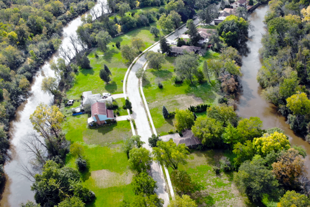 A different aerial view of the neighborhood shows a few homes that remain in the neighborhood, surrounded by grass and trees.