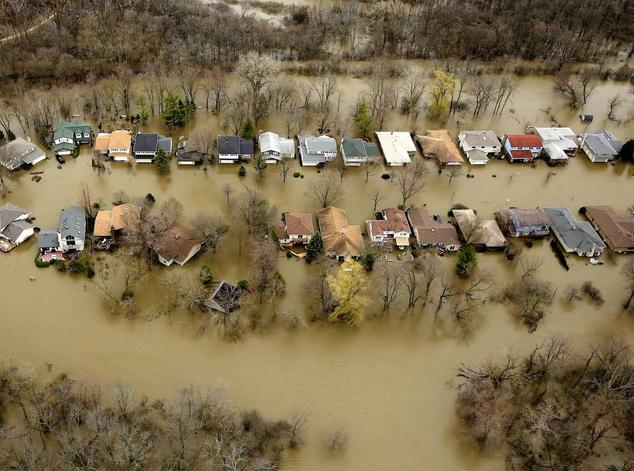 An aerial view of two rows of single-family homes that are completely surrounded by brown floodwaters.