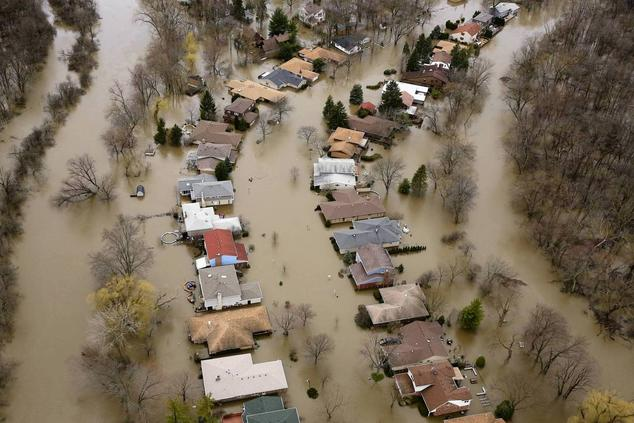 A second aerial view of two rows of single-family homes that are completely surrounded by brown floodwaters.