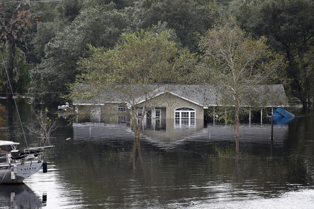 A boat floats outside of a one-story house that is flooded nearly up to its roof.