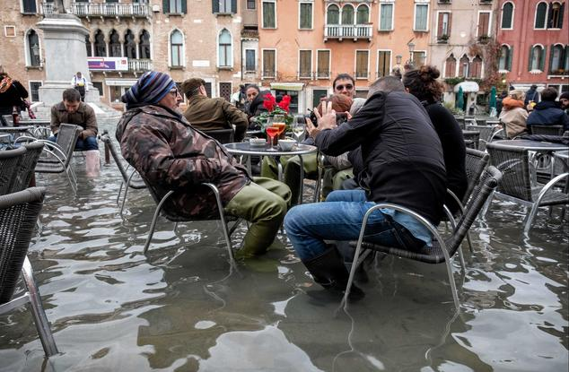 cafe patrons sitting in floodwaters in Venice, Italy