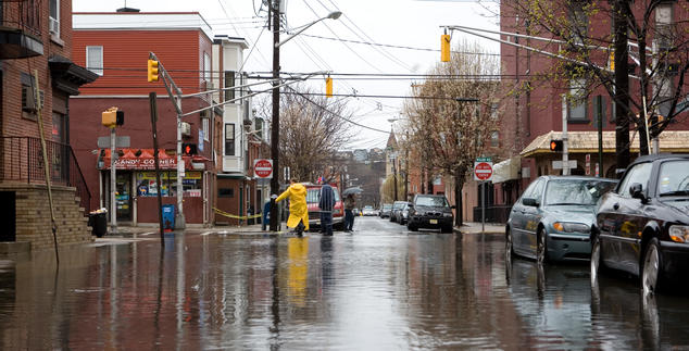 A person in a yellow raincoat stands in the middle of a flooded intersection