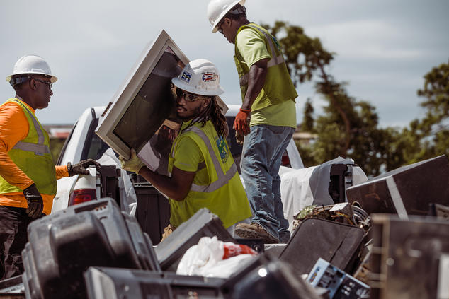 Three men unload hurricane debris from a pickup truck.