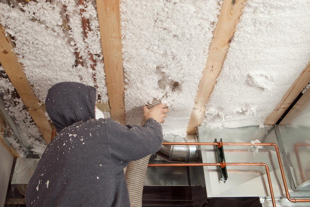 Worker installing insulation in a building