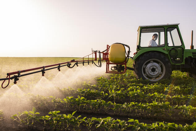 Tractor spraying pesticide over field