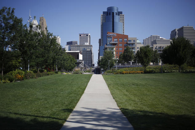 Cincinnati buildings, blue sky, green grass with paved sidewalk into the horizon.