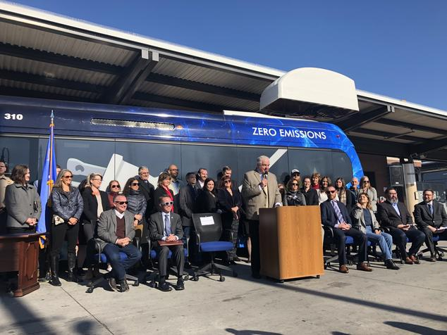 Gov. Sisolak speaking at a press conference in front of an electric bus