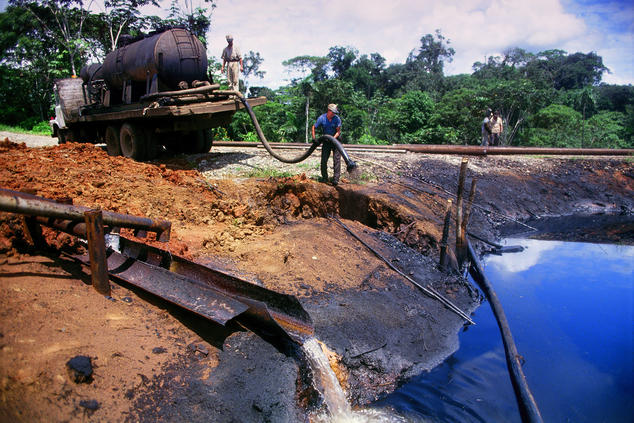 A worker siphons crude oil from a waster pit
