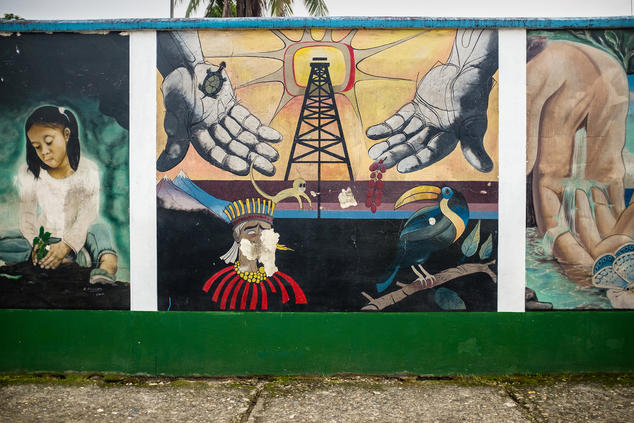 A mural depicting a child, an oil rig, and animals