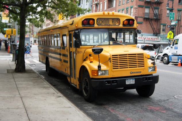 A yellow school bus is parked at the curb.