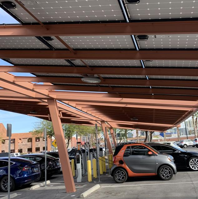 A small silver and orange electric car plugged in and charging in public parking lot in Las Vegas. The covering for the parking lot is made of solar panels.