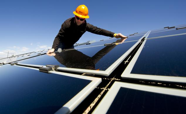 Construction worker testing solar panel