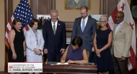 Picture of Mayor Bowser signing DC Green Bank Bill