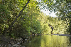 child playing on a rope swing over a river